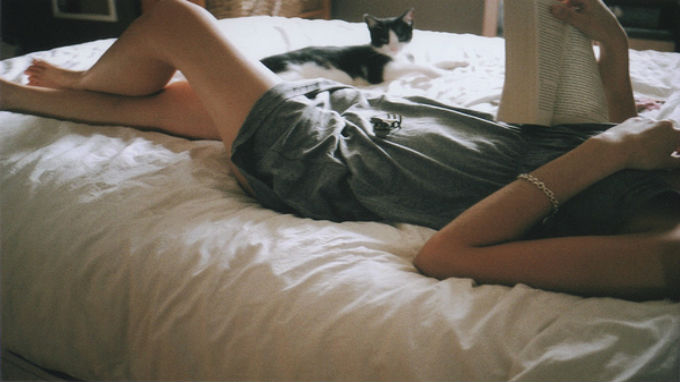 woman-laying-on-her-bed-reading-a-book-with-her-cat